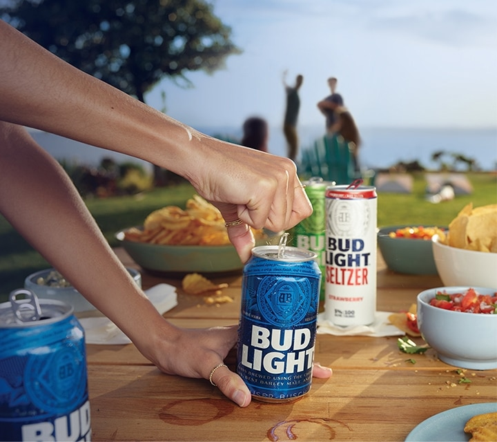 Can of Bud Light beer being opened on picnic table full of food and other Bud Light Products