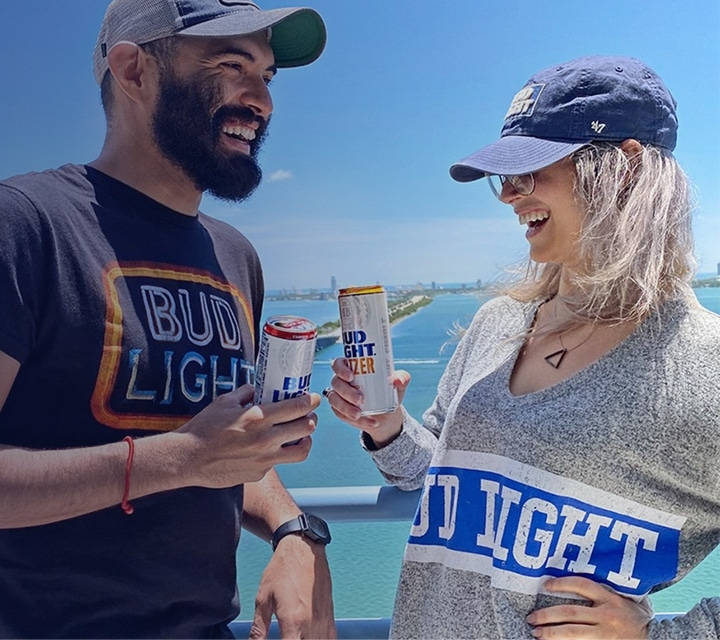 Man and woman dressed in Bud Light Merchandise, enjoying cans of Bud Light Seltzer
